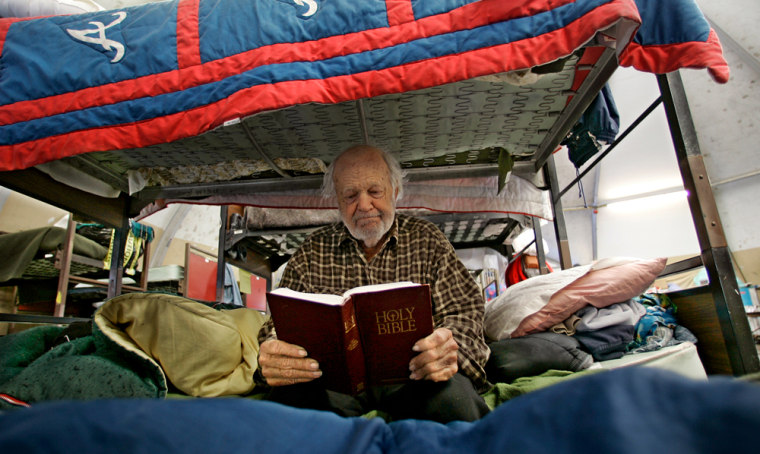 Roland Rode, originally from the Baltimore area but a long-time West Coast resident, reads the Bible while sitting in his bunk ata homeless shelter for veterans in San Diego onMarch 28.