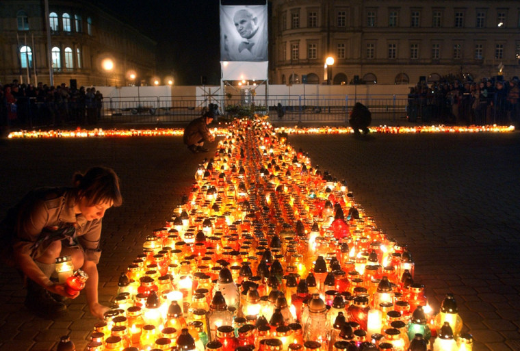 People light candles forming a giant cross in front of the late Pope John Paul II's portraiton the second anniversary ofhis death in Warsaw, Poland, on Monday.