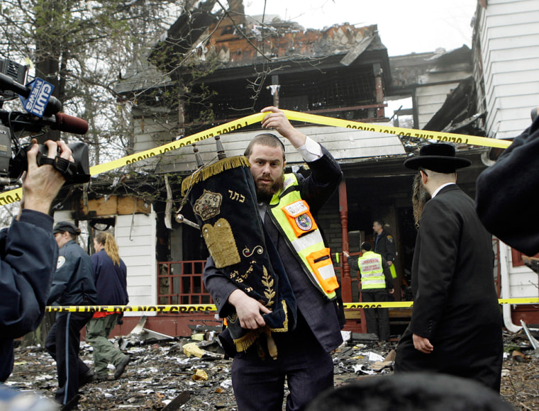 Morris Jacobowitz of the Chaverim Volunteer Emergency Services carries the Torah, which had been housed in a safe, as he leaves the burned ruins of the Bais Yehudi synagogue in Monsey, N.Y., on Monday.