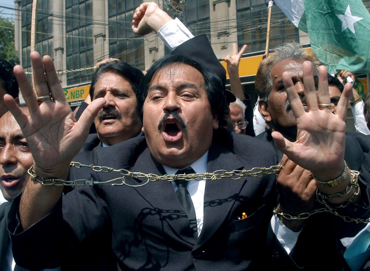 A Pakistani lawyer brandishes chains Tuesday as he shouts slogans during an anti-government rally in Karachi. Thousands of lawyers and flag-waving political activists rallied for the reinstatement of Pakistan's chief justice.