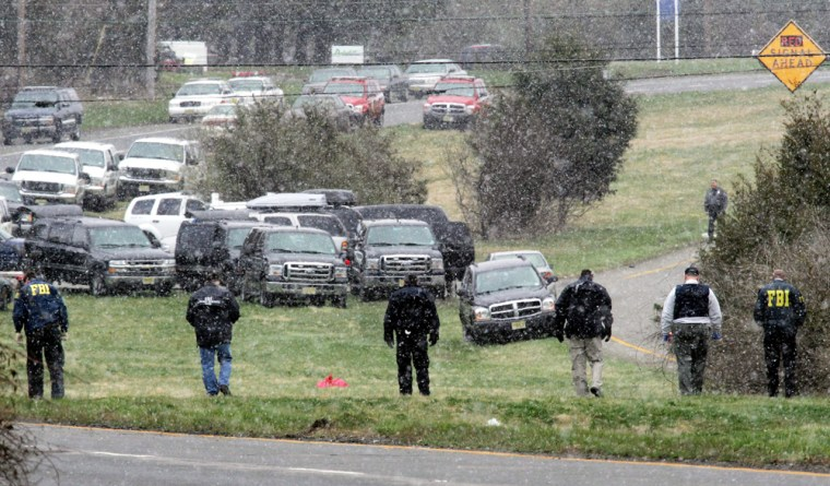 FBI agents look for evidence Thursday after an agent was killed in a shootout following a bank robbery inReadington, N.J.