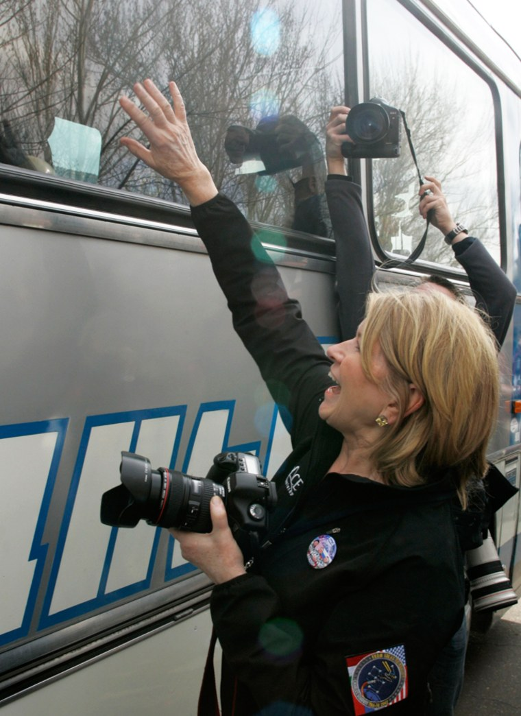 Martha Stewart waves to her friend, U.S. space tourist Simonyi, who is onboard a bus on the way for his final pre-launch preparation at Baikonur Cosmodrome