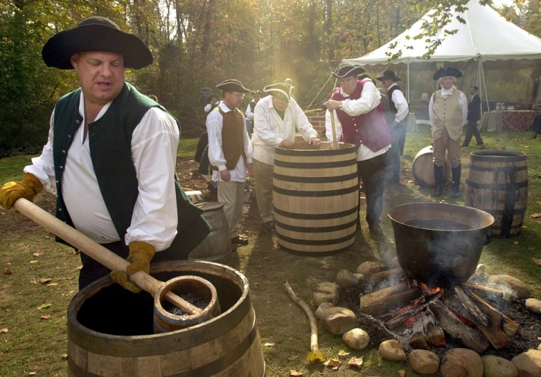 David Pickerell, master distiller for Maker's Mark, carries water to be boiled as he and other master distillers gather on the archaeology site of George Washington's distillery, in Mount Vernon, Va.