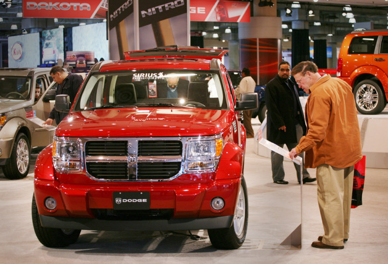 Visitors to the New York International Auto Show look at a Dodge Nitro on Friday. Even the company's top sales executive said the nonstop rumors of an imminent deal have had an impact.