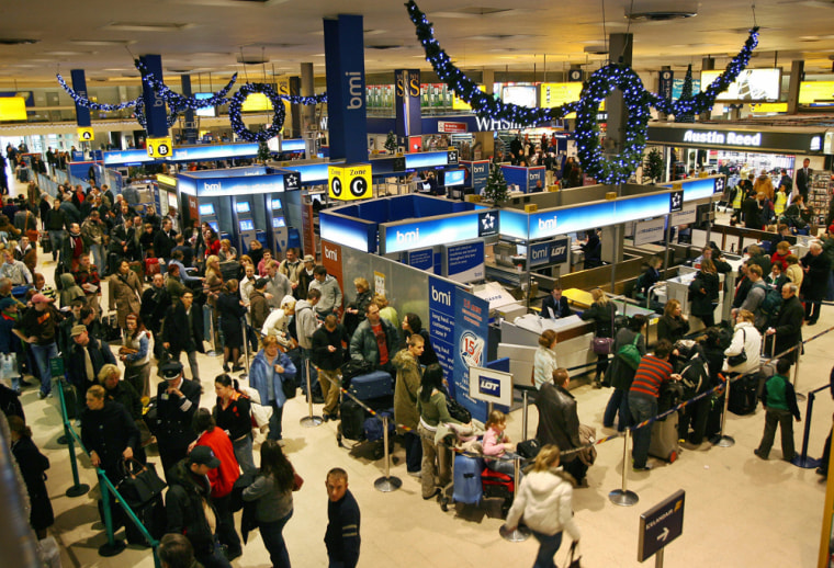 Passengers queue at the check-in desk in