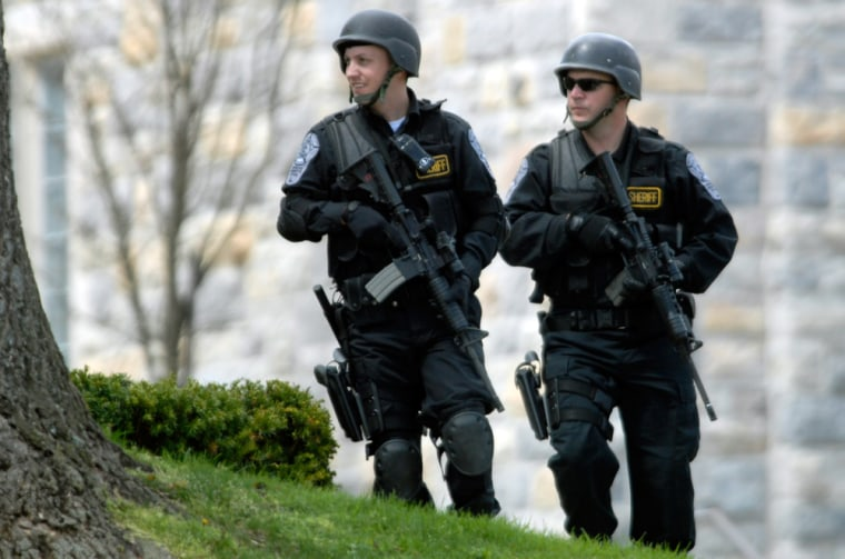 Security personnel patrol Monday near Norris Hall, the site of several deadly shootings on the campus of Virginia Tech in Blacksburg, Va.