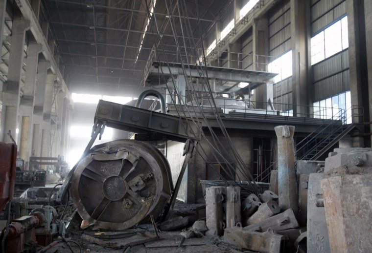 Damaged equipment is seen in a workshop after an accident at a steel factory in Tieling, in China's northeastern Liaoning Province, on Wednesday. A piece of heavy equipment at the plant broke off while transporting molten steel, killing at least 32 workers and injuring two others.