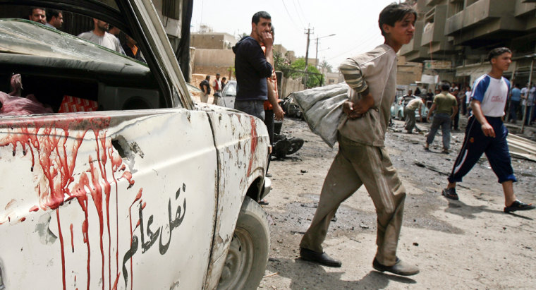 Residents gather at the scene of a deadly explosion in Baghdad onWednesday after a parked car exploded near a private hospital in the central neighborhood of Karradah.