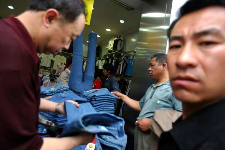 Customers look through clothing at a store in Beijing.China's sizzling economy jumped 11.1 percent in the first quarter, raising prospects the government will take further measures to cool growth.
