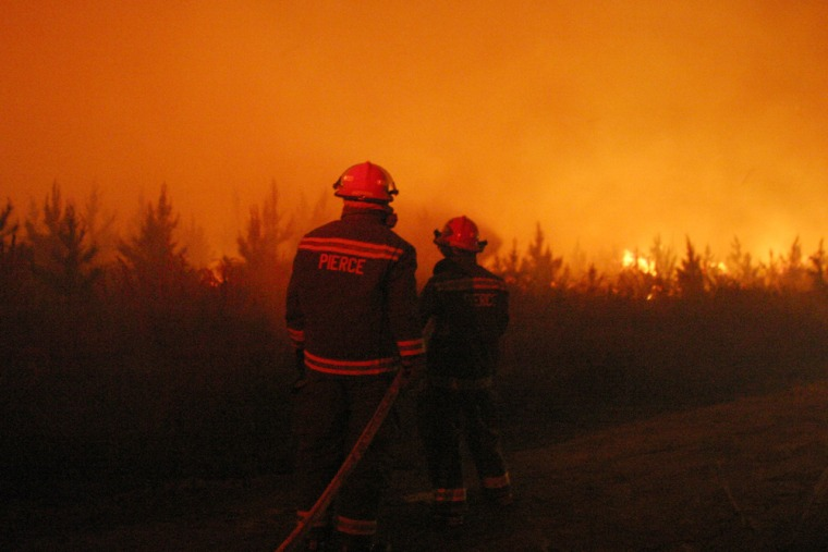 Firefighters on Wednesday battle one of the two wildfires near Waycross, Ga.