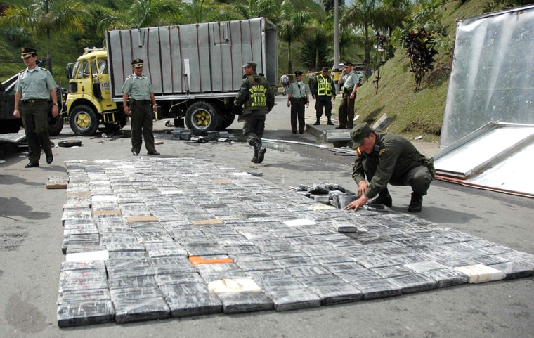 A policeman arranges packs of confiscated cocaine in Medellin