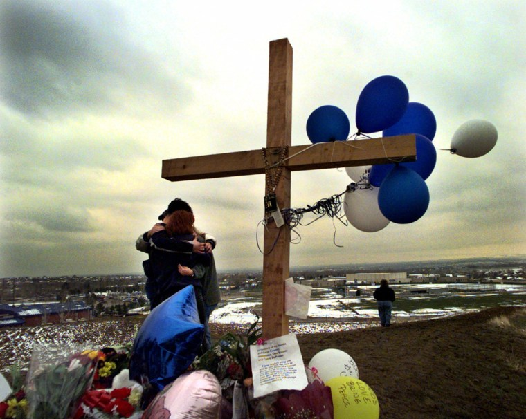 Students embrace each other at a makeshift memorial for their classmates killed at Columbine High School on a hilltop overlooking the school in Littleton, Colo., in April 1999.