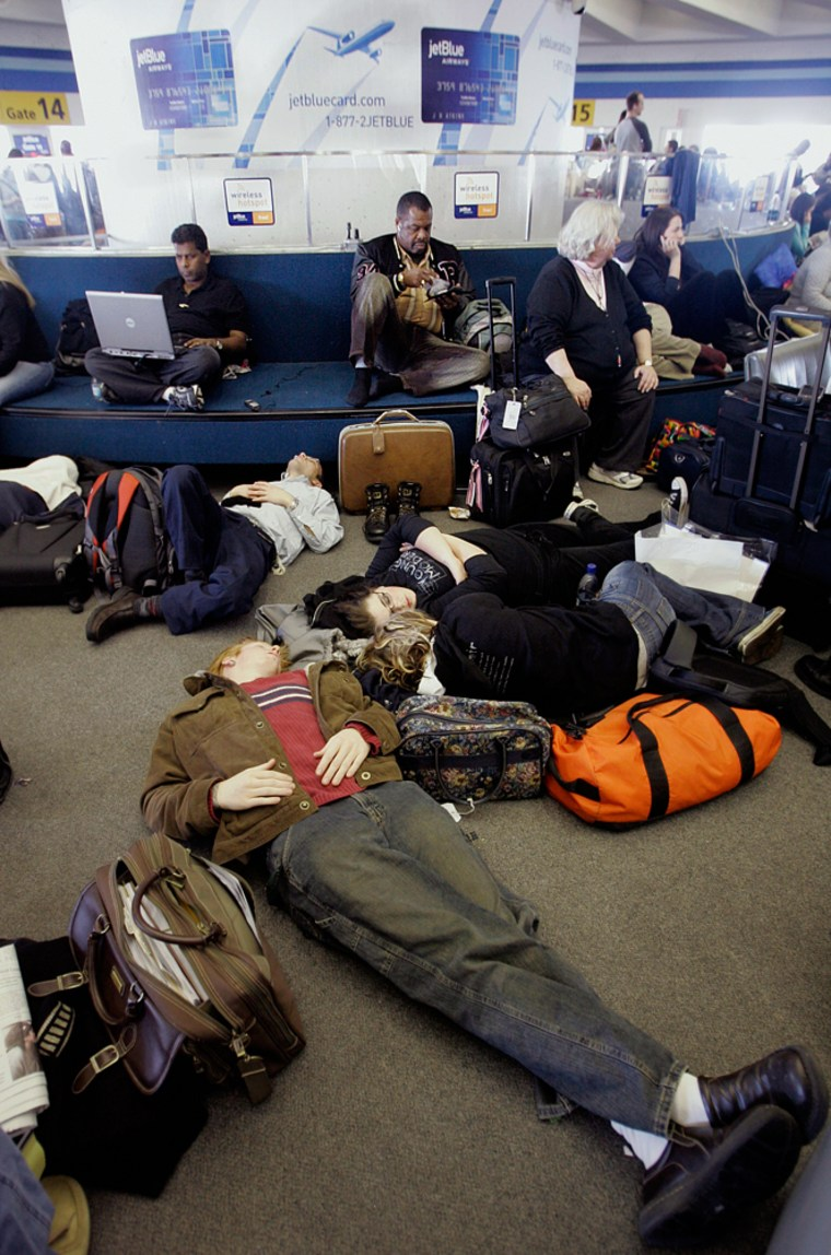 JetBlue passengers sleep and work on computers as they wait for flights at New York's John F. Kennedy Airport. A snow and ice storm back in February resulted in more than 1,000 flight cancelations and headaches for hordes of travelers.