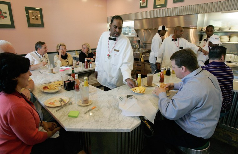 Waiter Melvin Henderson serves some cheese fries to a customer at the Camellia Grill diner asit reopens for business in New Orleans onFriday. The diner opened in 1946 and for generations was know for its hamburgers, omelets and pecan waffles.