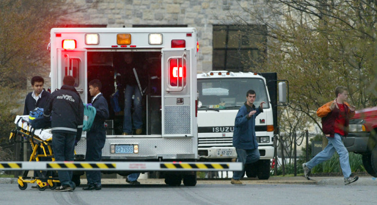 Virginia Tech students run from Norris Hall as an ambulance arrives on the scene in Blacksburg, Va., on April 16. That day's shooting — the worst of its kind in U.S. history — prompted the kinds of questions that have followed past massacres, namely, what is it about modern-day America that provokes such random violence?
