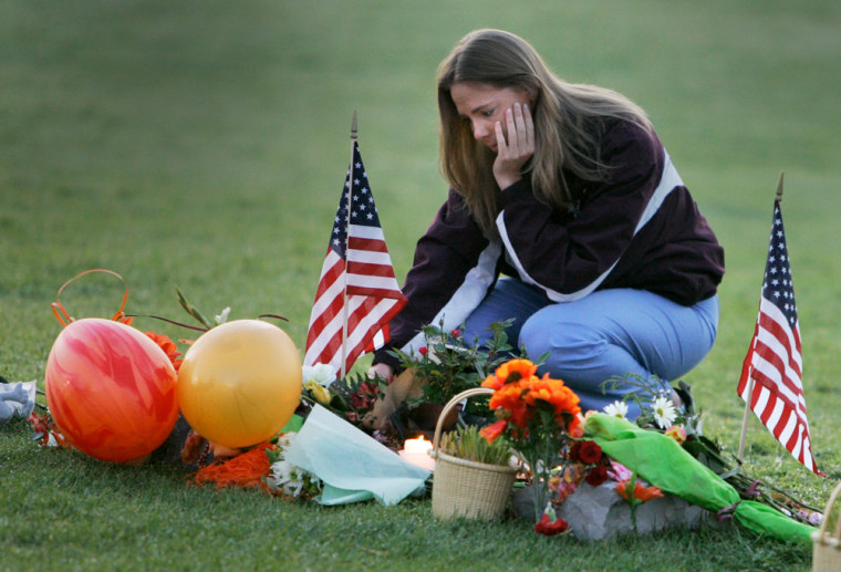 Virginia Tech alumnus Michelle Creamer, 25, of Bracey, Va., visits the makeshift memorial in front of Burruss Hall on the campus of Virginia Tech University in Blacksburg, Va., on Saturday.