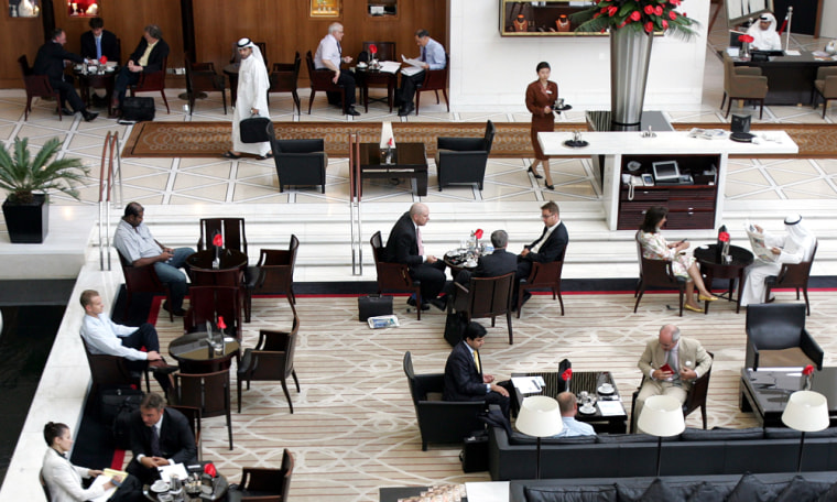 The lobby of the Emirates Towers hotel in Dubai, United Arab Emirates, is crowded with business people holding meetings. Sustained high oil prices have left state-owned investment companies in the Gulf with a lot of buying power.