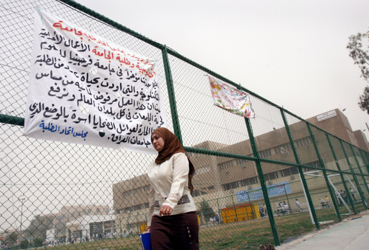 An Iraq student walks past a banner expressing condolences for the shooting victims at Virginia Tech, on the fence of Baghdad Technology University, on Tuesday. Universities and academics have been among the hardest hit by the violence plaguing Iraq, but students still found themselves saddened by last week's massacre at theU.S. university.