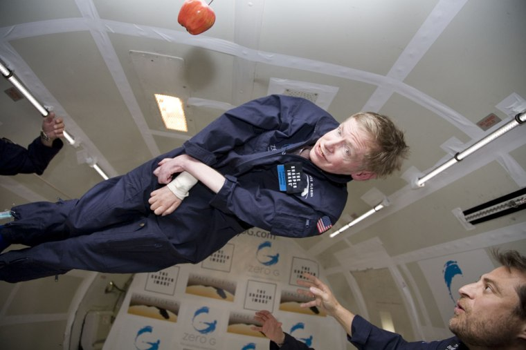 Physicist Stephen Hawking flashes a grin as he floats in weightlessness on Thursday, with Zero Gravity Corp.'s Peter Diamandis looking on from right. The apple is a tribute to Isaac Newton and his theories of gravity.