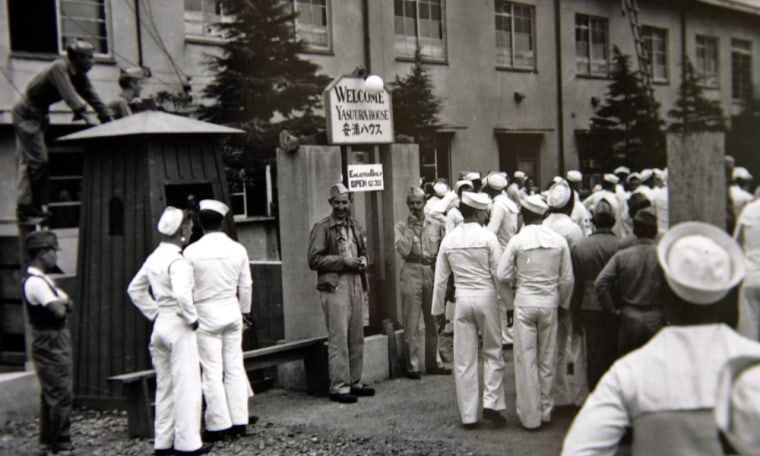 """In this undated image released by the Yokosuka City Council in Japan, U.S. sailors gather in front of a Yasu-ura House """"comfort station"""" in Yokosuka, south of Tokyo."""
