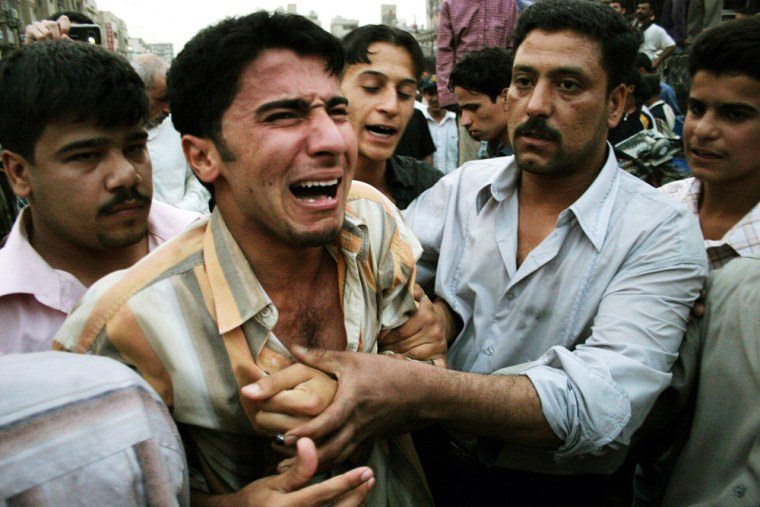 Iraqis try to comfort a weeping man at t