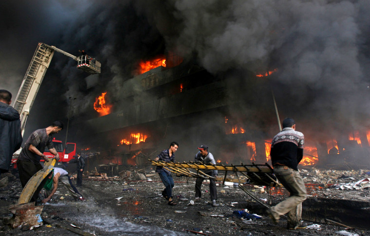 Firemen and residents rush to a burning building after twin bomb attacks at Shorja market in Baghdad