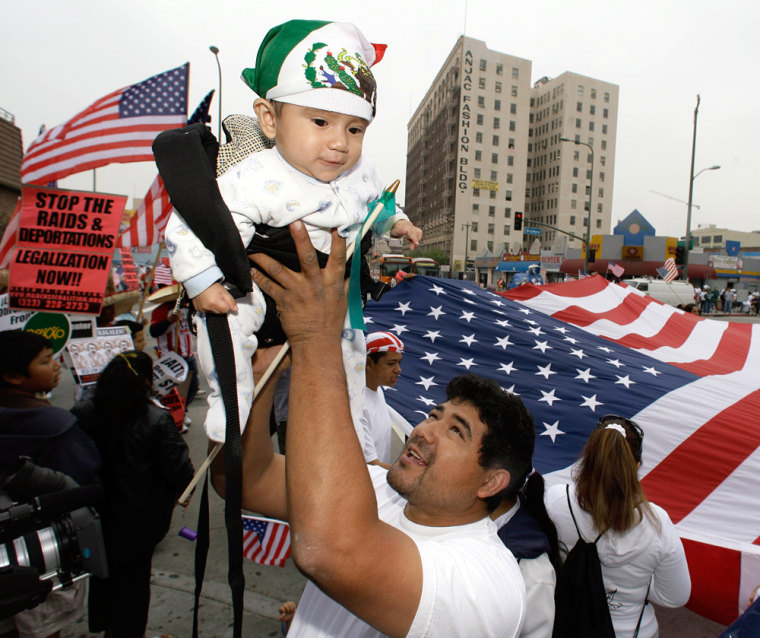 Marcelino Rodriguez, 36, from Jalisco, Mexico, and a U.S. resident for 28 years, lifts his 5-month-old son, Francisco, as demonstrators gather on Tuesday to rally in downtown Los Angeles.