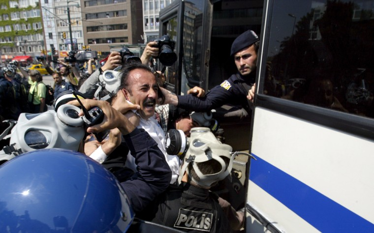 Turkish riot police detain a protester a