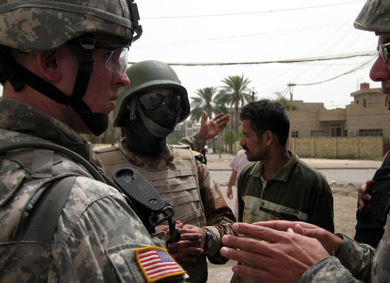 A colonel in the Iraqi armyspeaks with members of the U.S. Army's 2nd Battalion, 32nd Field Artillery, 2nd Brigade, 1st Infantry Division in the Hateen neighborhood of western Baghdad on April 29.