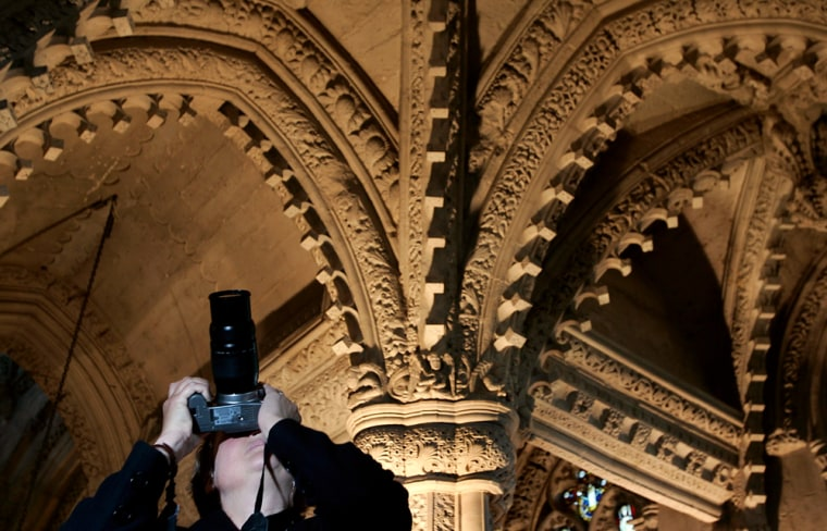 A tourist takes a photograph of the cube carvings on the chapel arches at Rosslyn Chapel near Edinburgh
