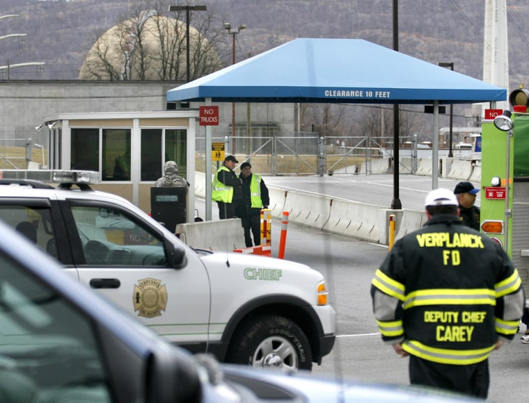 A reactor within the Indian Point nuclear complex near Buchanan, N.Y., is seen in the background as officials gather at an entrance during a minor fire inside in 2007.