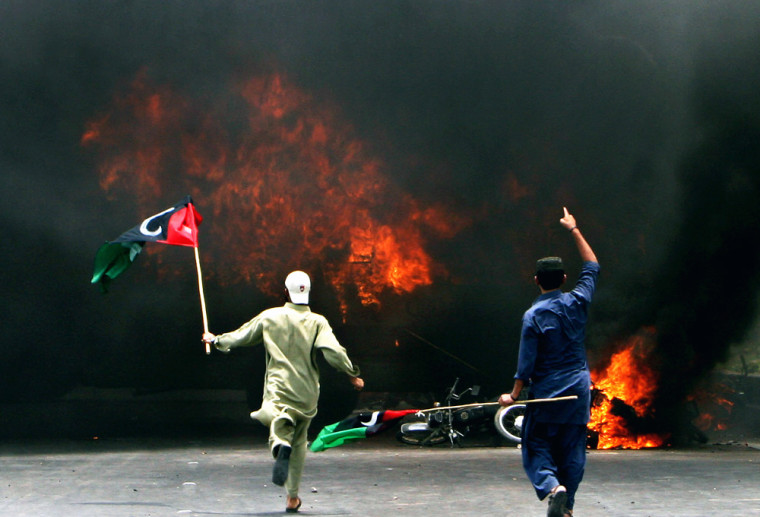 Opposition party supporters walk after setting on fire a vehicle during a gunbattle between rival groups in Karachi, Pakistan, on Saturday.