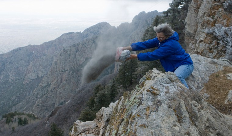 Bobbi Burg, vice president of the International Scattering Society, scatters cremated remains from the top of the Sandia Mountains, outside Albuquerque, N.M. Customers can pay to have their loved one's ashes scattered at locations around the world.