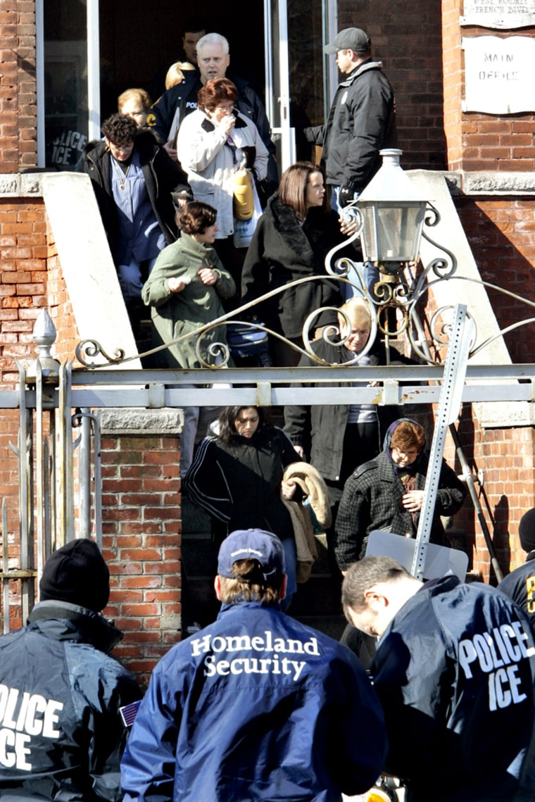 Employees are escorted out after an early morning raid by federal immigration officials at the Michael Bianco Inc. textile plant in New Bedford, Mass., on March 6. Some illegal immigrants are drawing up legal instructions designating someone to take care of their children if the parents are jailed or deported.