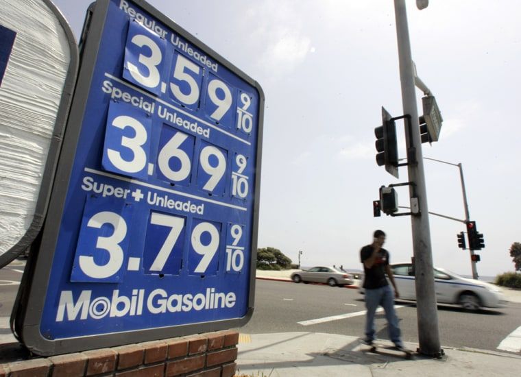 A skateboarder rolls past a sign showing gas prices in Laguna Beach, Calif., on Wednesday. Gasoline prices reach new highs leading up to the Memorial Day travel weekend.