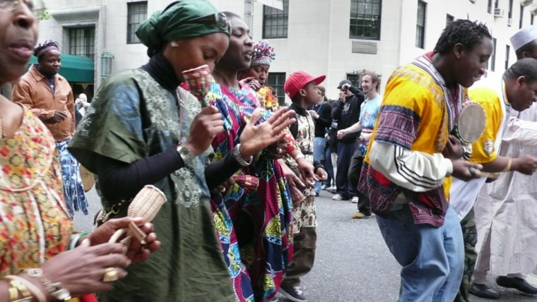 "Playing instruments and clad in traditional African dress, ""Dance Parade"" demonstrators  groove their way down New York City streets to call for an end to Prohibition-era laws that forbid dancing everywhere except in those establishments possessing a special license."