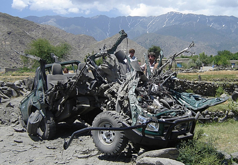 Afghan men inspect a vehicle damaged by