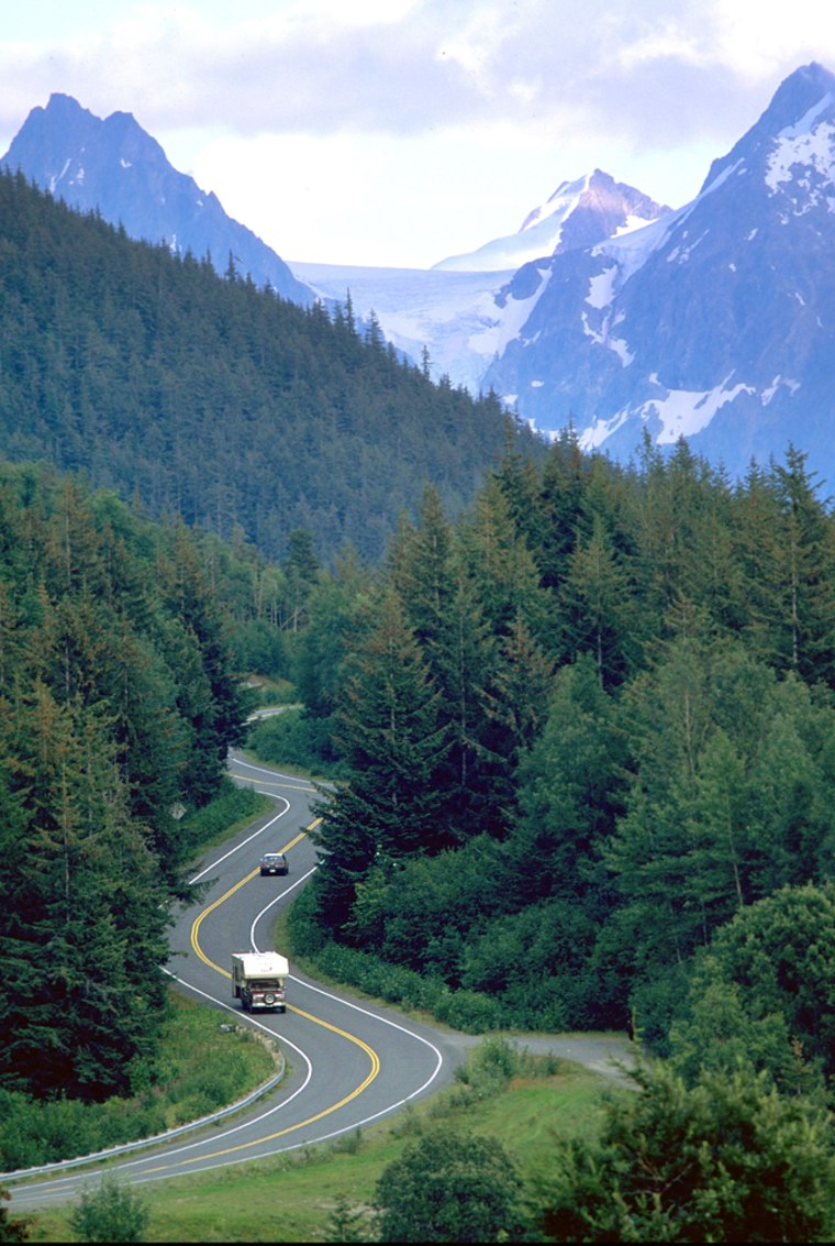Cars wind down through the mountains from Eureka Summit on Alaskas Glenn Highway, where road travelers enjoy incredible vistas including nearby Matanuska Glacier.