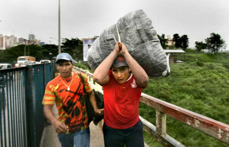 """Two men called """"sacoleiros"""" transport goods from Paraguay's Ciudad del Este to Brazil's Foz do Iguazu by way of the """"Friendship Bridge"""" on Monday."""