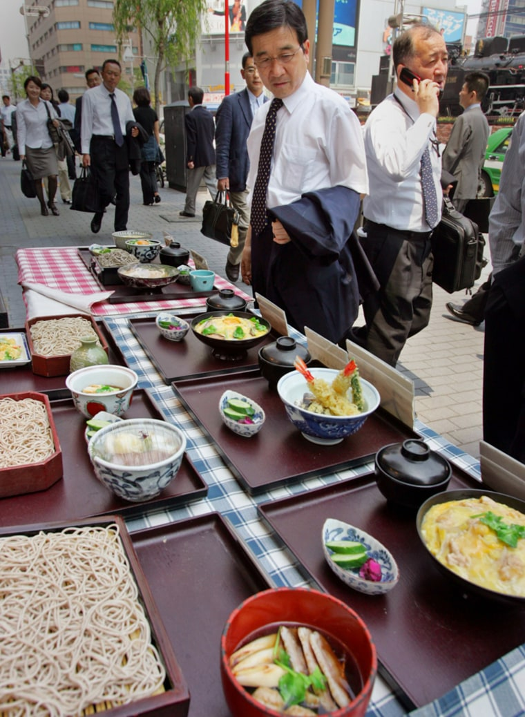 A Japanese businessman looks at samples of a lunch menu in front of a restaurant as another man walks by speaking on his mobile in Tokyo this week. Now a system lets thecalorie-consciousphone in their eating habits.