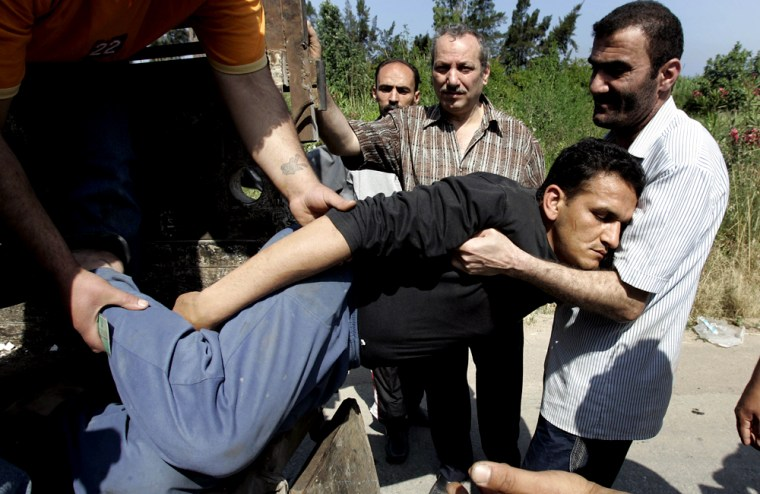 Two Palestinian men help a man who collapsedflee from the Palestinian refugee campNahr el-Bared on Thursday.