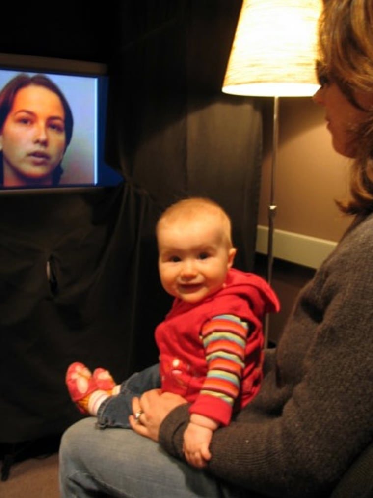 A baby sits on a caregiver's lap before a television screen used in a University of British Columbia study to see how babies watch the silent faces of bilingual speakers reciting sentences in both English and French. The caregiver wears darkened sunglasses to prevent influencing the baby.