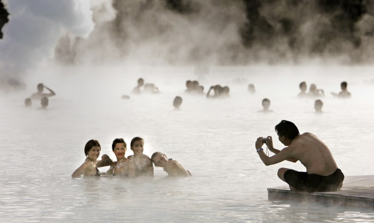 Bathers pose for a photo as they swim in the geothermal hot springs at Iceland's Blue Lagoon near Grindavik
