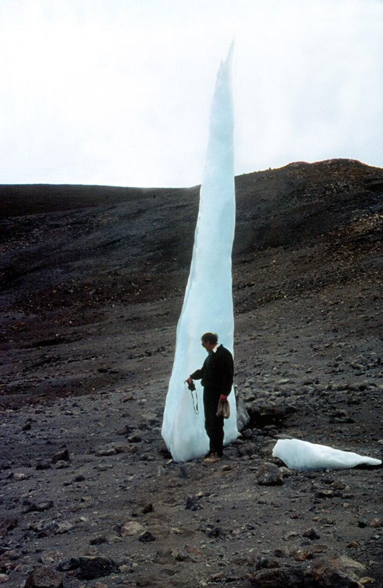 Lonnie Thompson, picked for a 2007 Medal of Science, stands next to an ice spire at Mount Kilimanjaro in Tanzania. The spire, and others like it, was left bythe mountain'sreceding glacier.