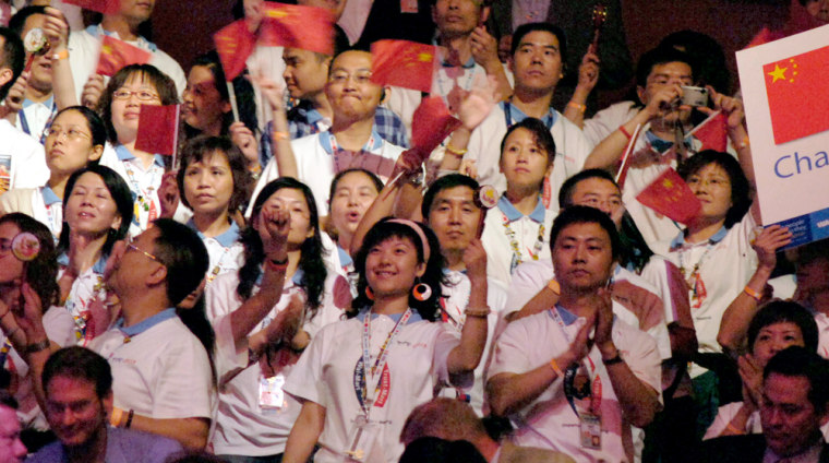 Wal-Mart employees from China wave flags before the company's annualshareholders meeting, held in a basketball arena. More than 15,000 employeesand other shareholders attended theevent.