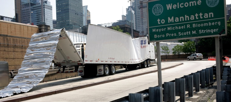 A damaged truck rests in a lane outside New York's Lincoln Tunnel onThursday after a driver,whose rig was 6 inches too tall for the tunnel, drove its entire 1.5-mile length, peeling the trailer's roof and ripping off decorative ceiling tiles.
