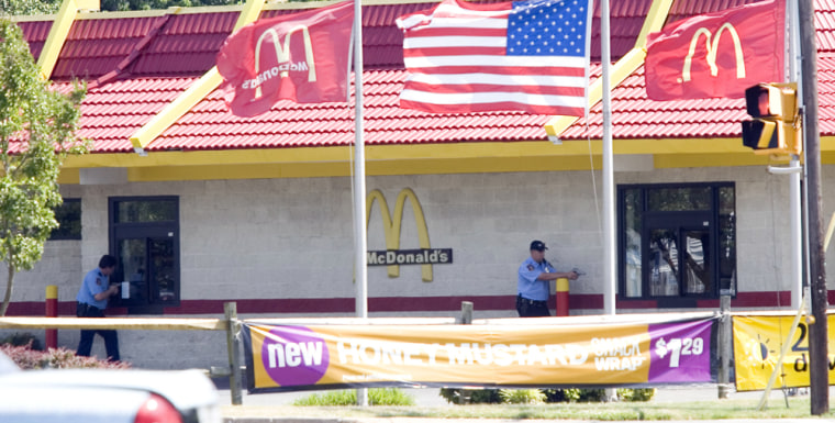 Hampton police officers stand outsidethe McDonald's restaurant Monday where the supposed hostage standoff unfolded.