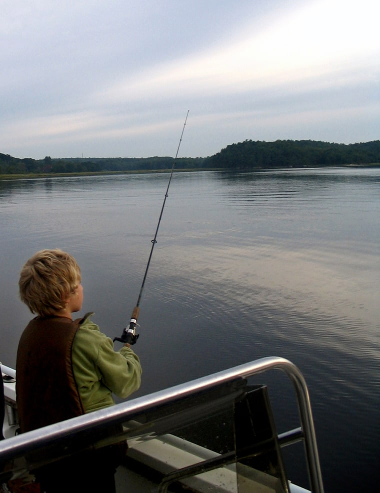 Nathaniel Harpaz, 8, waits for a bite just after sunrise on the Kennebec River in Bath, Maine.