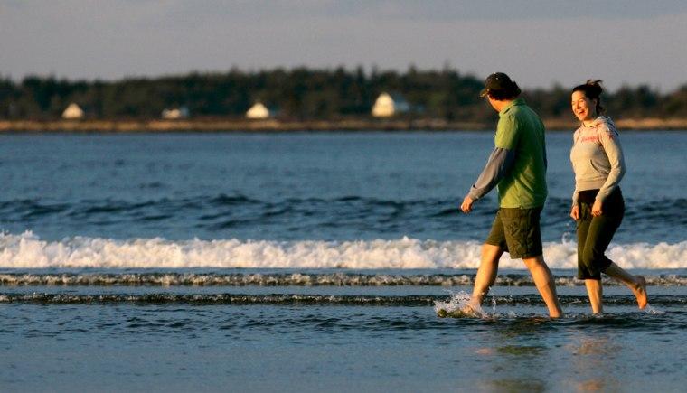 Friends enjoy a late afternoon walk at Popham Beach State Park, in Phippsburg, Maine.