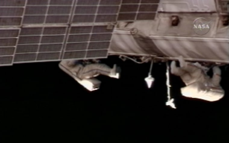 Spacewalkers Fyodor Yurchikhin and Oleg Kotov roll out data cable along the exterior of the international space station on Wednesday.